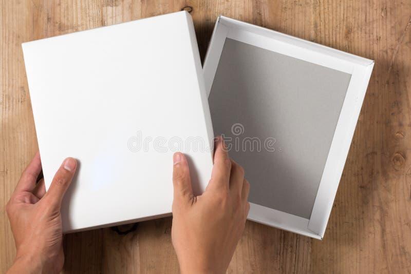 Boîte en carton ouverte par main sur le fond en bois photos libres de droits