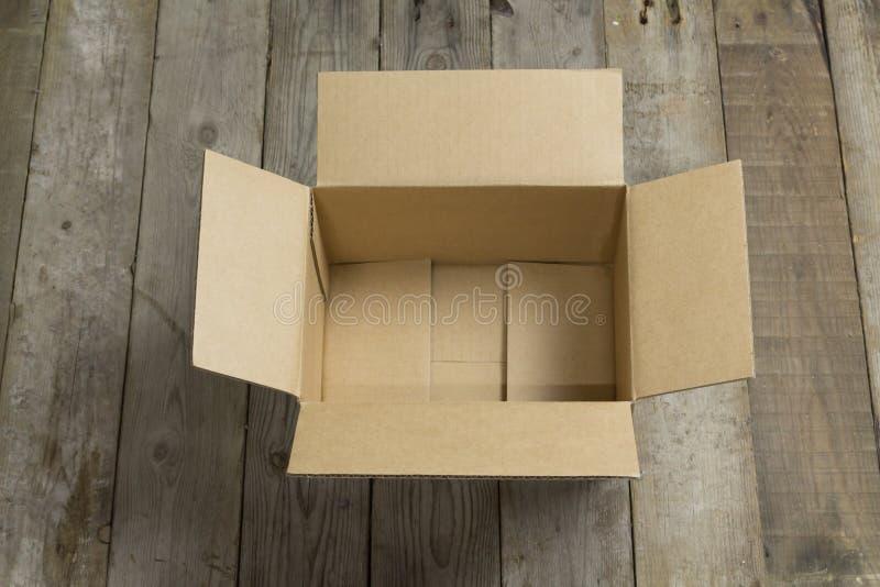 Boîte en carton ouverte sur en bois image libre de droits