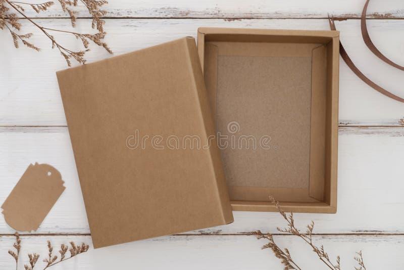 Boîte en carton ouverte sur le fond en bois blanc avec l'herbe sèche photo stock
