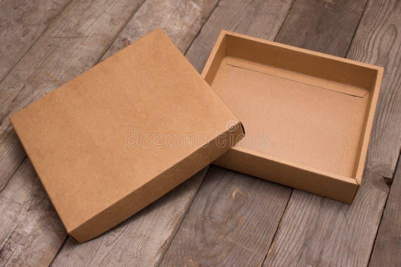 Boîte en carton ouverte sur le fond en bois photographie stock libre de droits