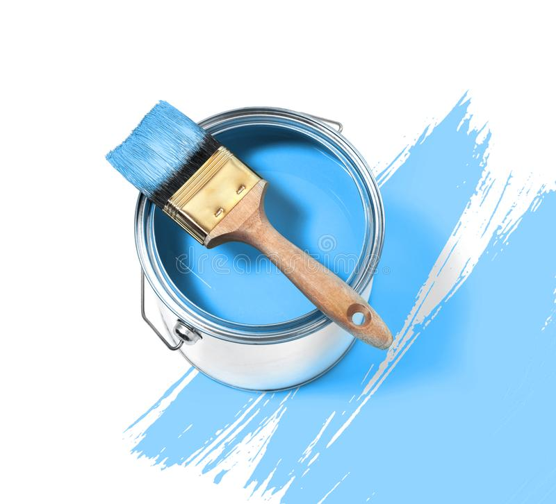 Boîte en fer blanc de peinture bleue avec la brosse sur le dessus sur un fond blanc avec photo libre de droits