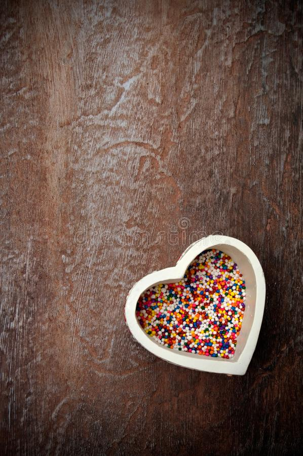 Boîte en forme de coeur blanche à sucrerie avec les sucreries miniatures sur le vieux bois superficiel par les agents images libres de droits