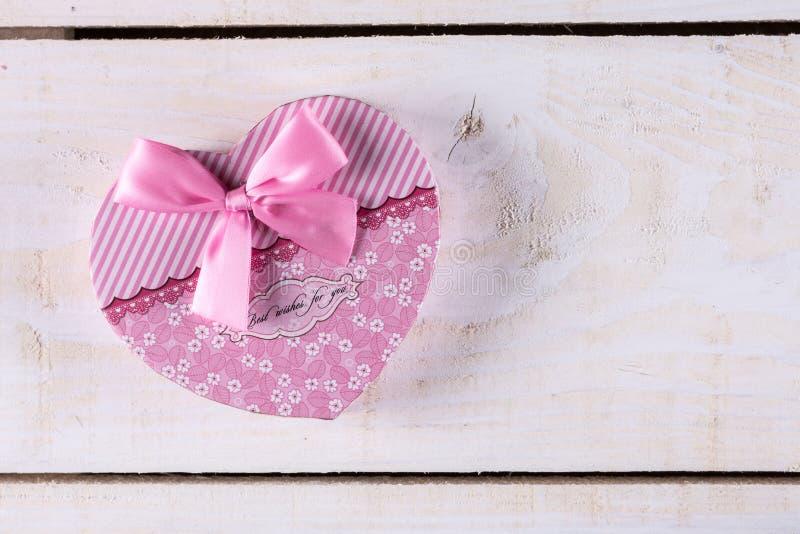 Boîte en forme de coeur de couleur rose avec l'arc rose au-dessus du fond en bois photographie stock libre de droits