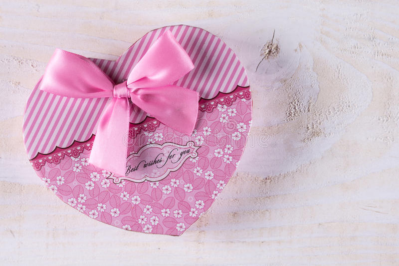 Boîte en forme de coeur de couleur rose avec l'arc rose au-dessus du fond en bois photographie stock