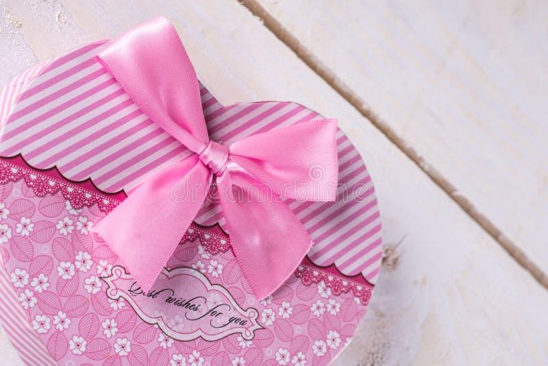 Boîte en forme de coeur de couleur rose avec l'arc rose au-dessus du fond en bois image libre de droits
