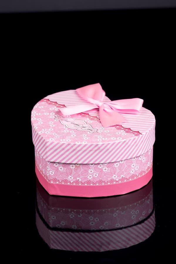 Boîte en forme de coeur rose au-dessus de fond noir avec des réflexions photos libres de droits