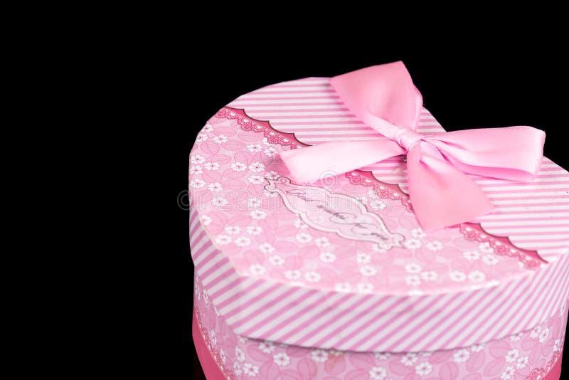 Boîte en forme de coeur rose d'isolement au-dessus du fond noir avec des réflexions photo libre de droits