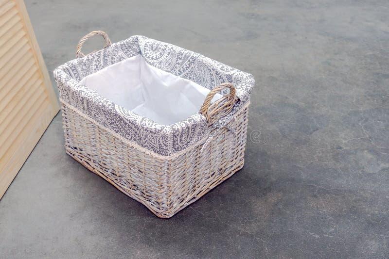 Boîte en osier de type de Boho de rotin, avec des poignées sur le plancher en béton photo stock