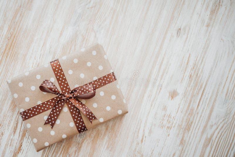 Boîte en papier de métier, papier d'eco sur la table en bois Vue supérieure Boîte-cadeau emballé en papier de Brown avec l'arc de image libre de droits