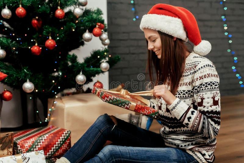 Boîte heureuse de cadeau de Noël d'ouverture de femme fille dans le chandail avec photographie stock libre de droits