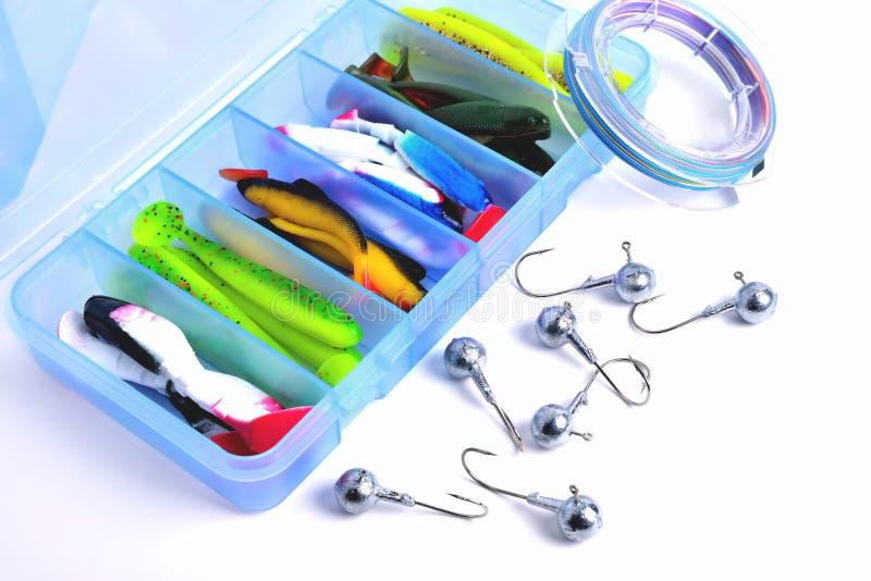 Boîte pour pêcher des accessoires avec des amorces de silicone à l'intérieur, crochets de gabarit, bobine tressée sur un fond bla images stock