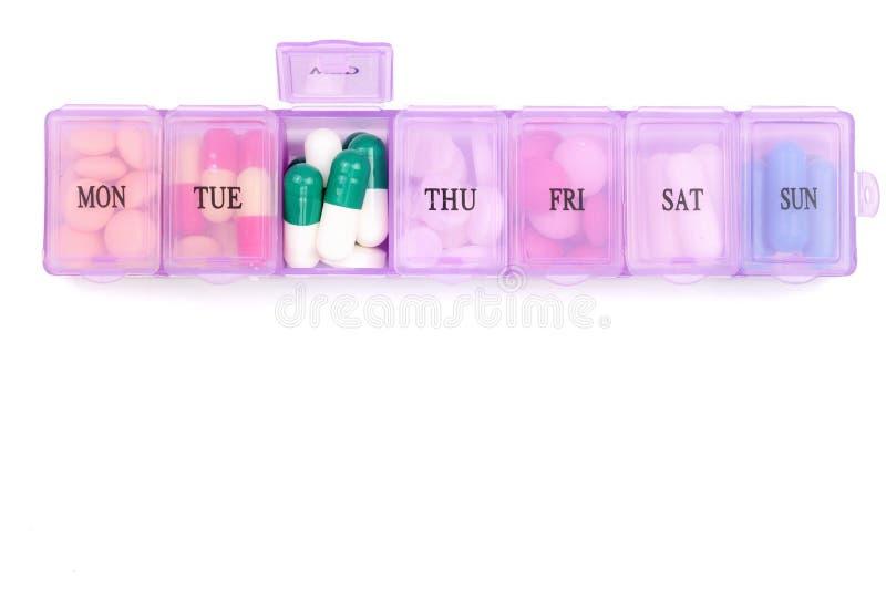 Boîte quotidienne de pilule avec les pilules médicales d'isolement sur le fond blanc avec l'espace de copie pour votre texte Vue  images stock