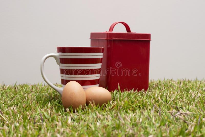Boîte rouge, tasse de café et deux oeufs photos libres de droits