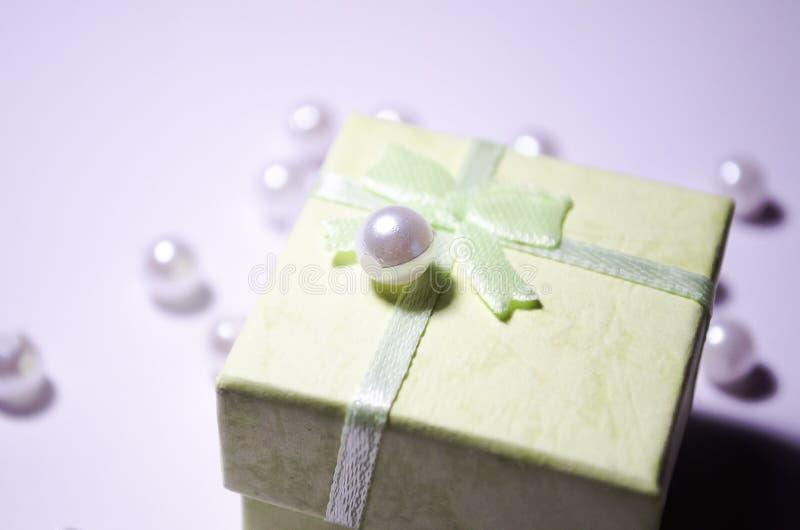 Boîte verte avec une perle Perle sur la boîte Perle en plastique E Programmes blancs images libres de droits