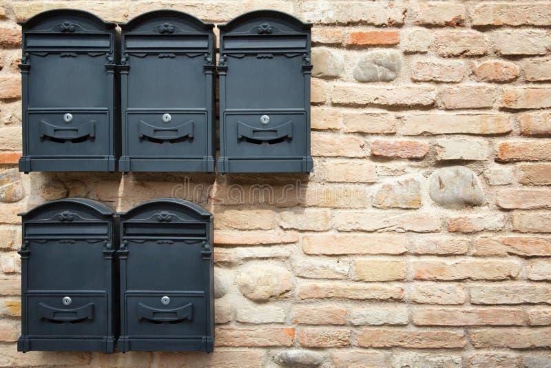 Boîtes aux lettres noires contre le mur de briques images stock