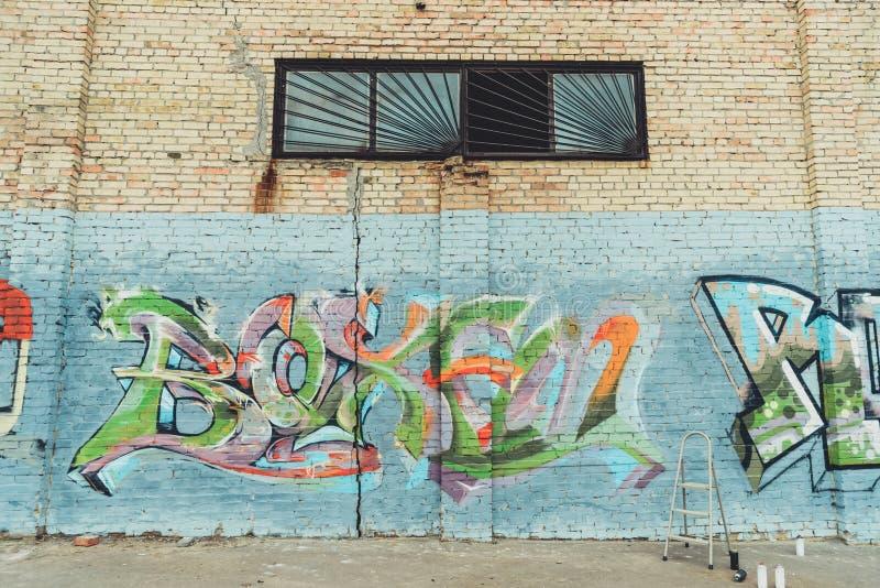 boîtes avec la peinture et l'échelle de jet près du graffiti coloré sur le mur du bâtiment photos stock