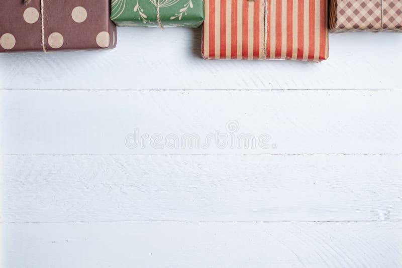 Boîtes colorées avec des cadeaux sur un fond en bois blanc photo libre de droits