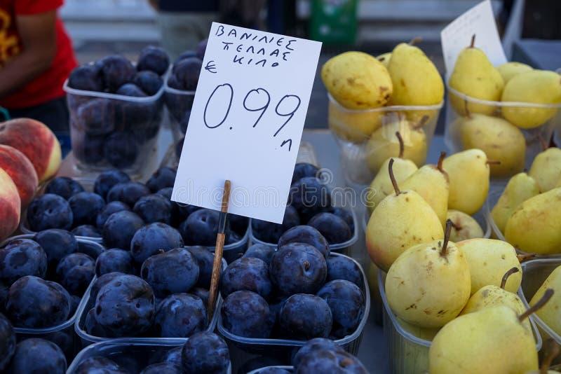 Boîtes complètement de prunes ambres noires fraîches avec le revêtement cireux blanc poussiéreux se vendant à côté des poires et  photos libres de droits