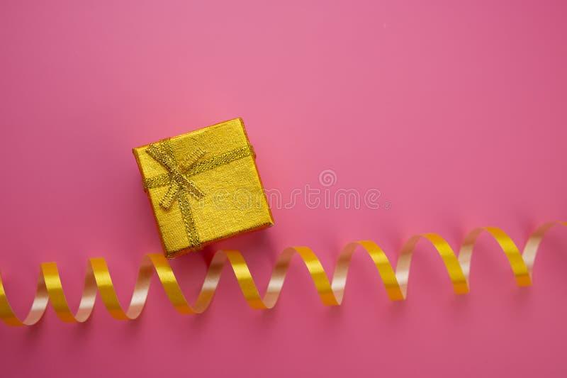 Boîtes d'or avec des cadeaux de Noël et mensonge d'or de ruban sur une goupille photographie stock
