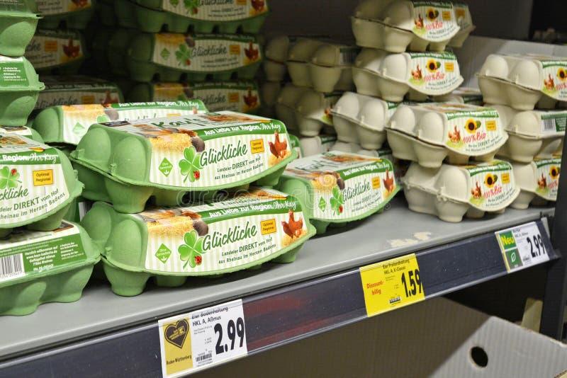 Boîtes de cage libres et d'oeufs organiques prétendant venir des poulets heureux en dépit de ne pas être oeufs libres de gamme image libre de droits