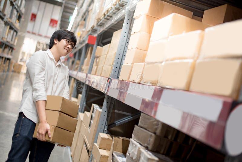 Boîtes de papier de transport de jeune homme asiatique dans l'entrepôt images libres de droits