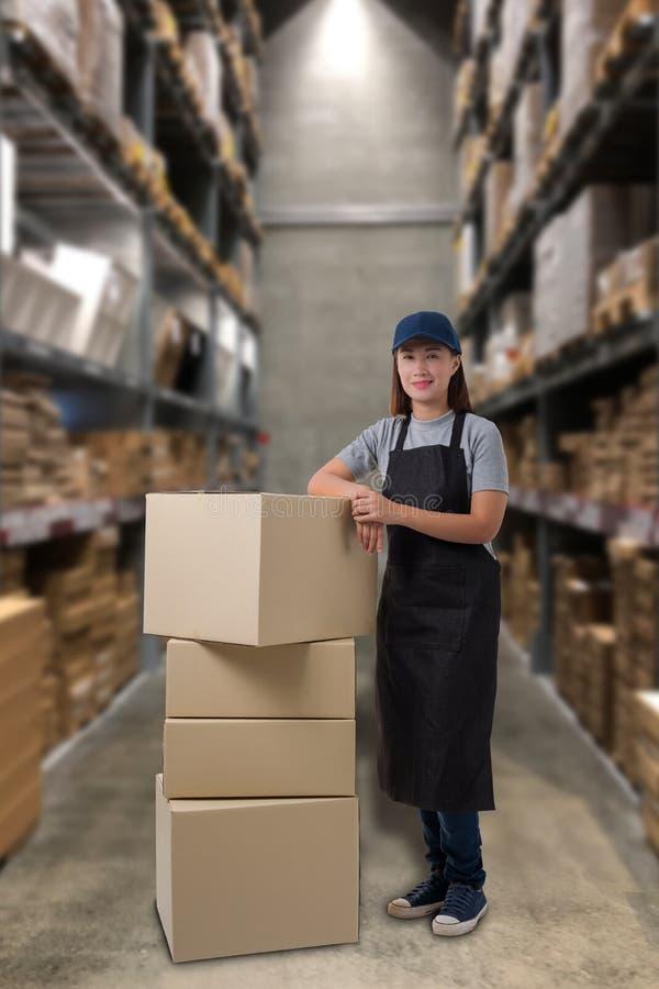 Boîtes de personnel féminin et de colis dans l'entrepôt image stock