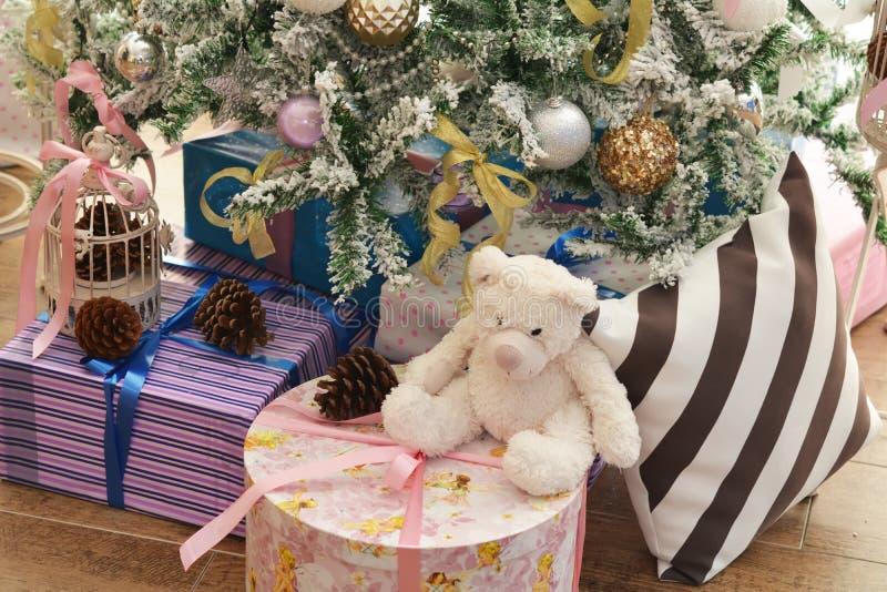 Boîtes de présents sous l'arbre de Noël vert décoré des jouets de fête photographie stock libre de droits