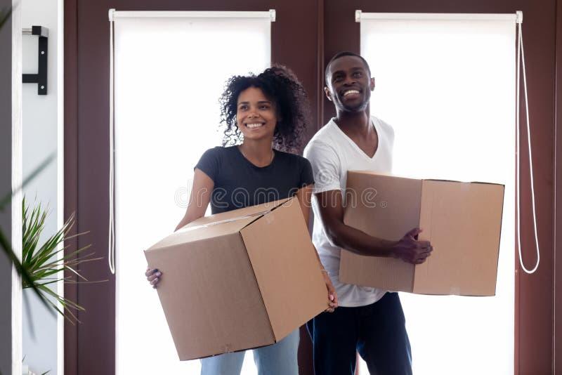 Boîtes de transport de couples noirs enthousiastes entrant le grand couloir moderne de maison image libre de droits
