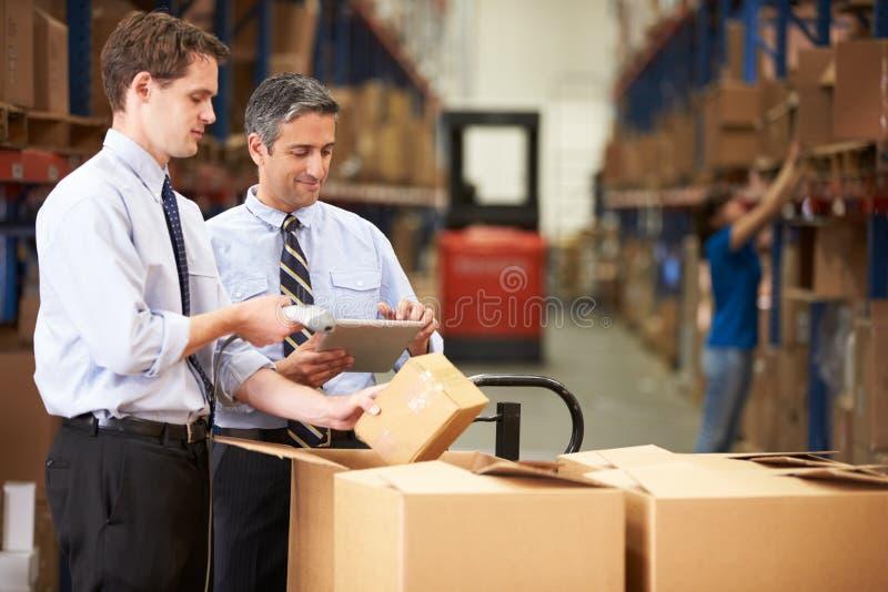 Boîtes de vérification d'hommes d'affaires avec la Tablette et le scanner de Digital photographie stock libre de droits