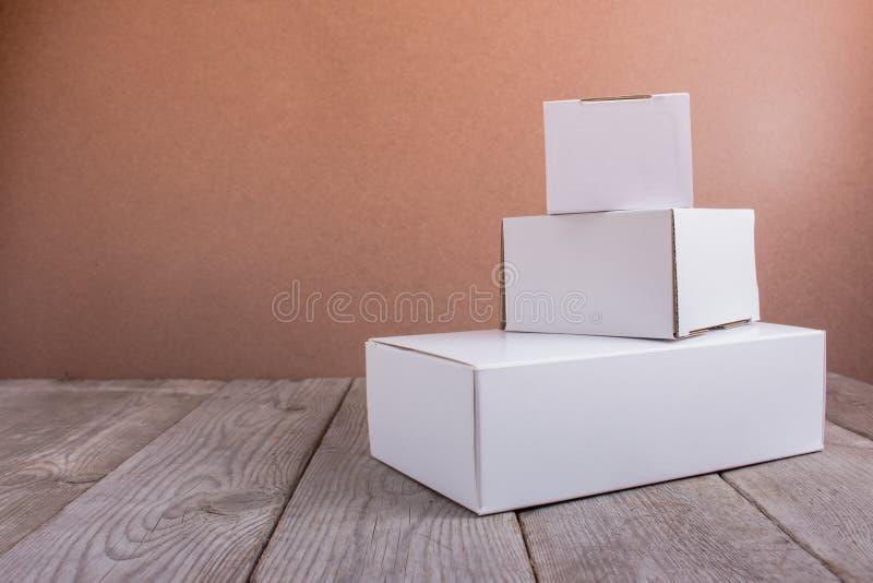 Boîtes en carton blanches sur le fond en bois photos libres de droits