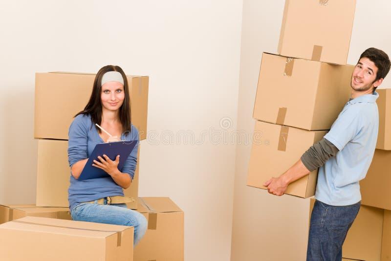Boîtes en carton de transport de jeunes couples à la maison mobiles photo libre de droits