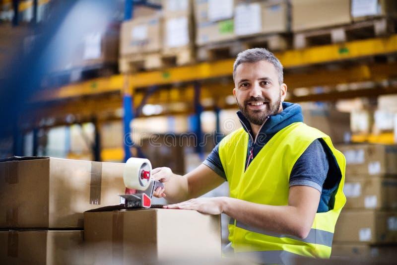 Boîtes en carton masculines de cachetage de travailleur d'entrepôt images stock