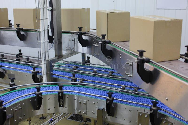Boîtes en carton sur la bande de conveyeur dans l'usine photos stock