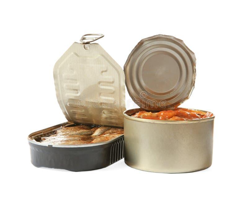 Boîtes en fer blanc ouvertes de poissons à la sauce tomate et aux esprots sur le blanc photo stock