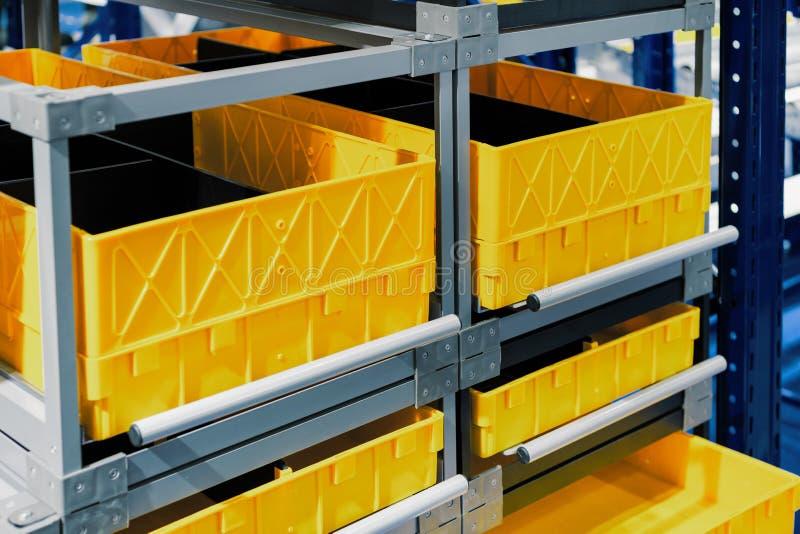 Boîtes en plastique jaunes dans les cellules de l'entrepôt automatisé photographie stock