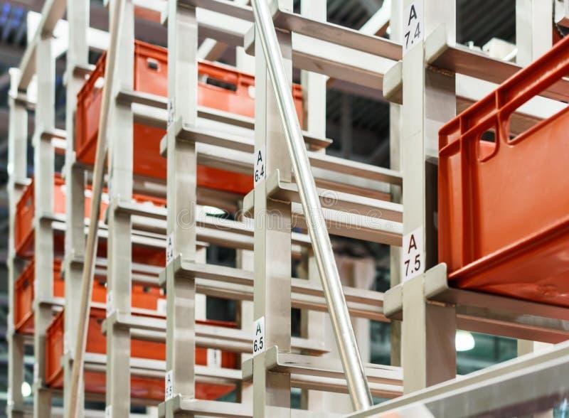 Boîtes en plastique rouges dans les cellules de l'entrepôt automatisé photo stock
