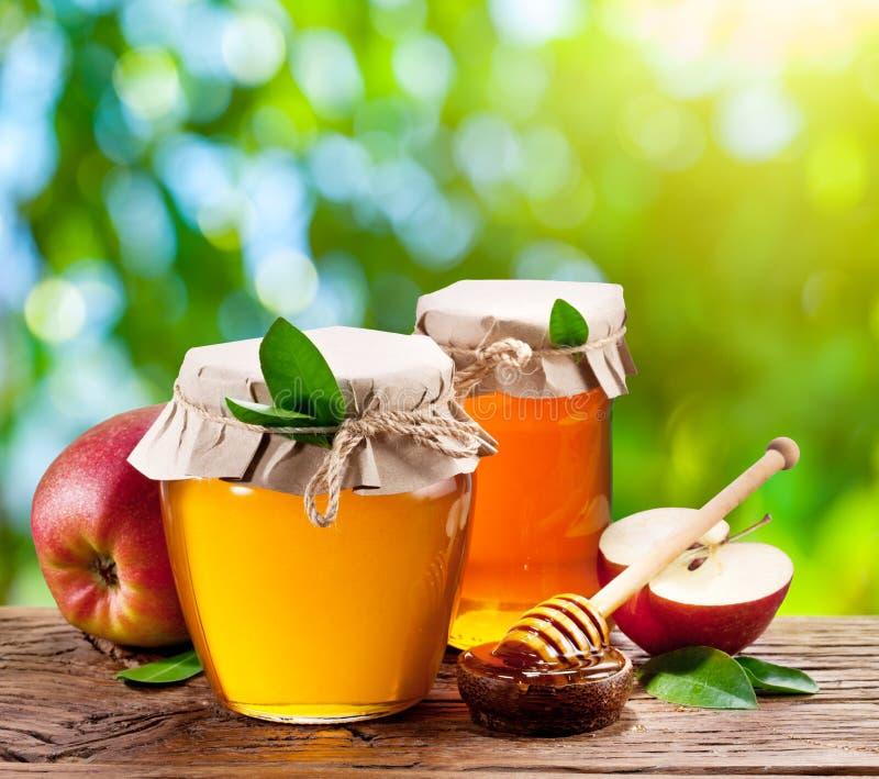 Boîtes en verre complètement de miel, de pommes et de peignes photographie stock libre de droits