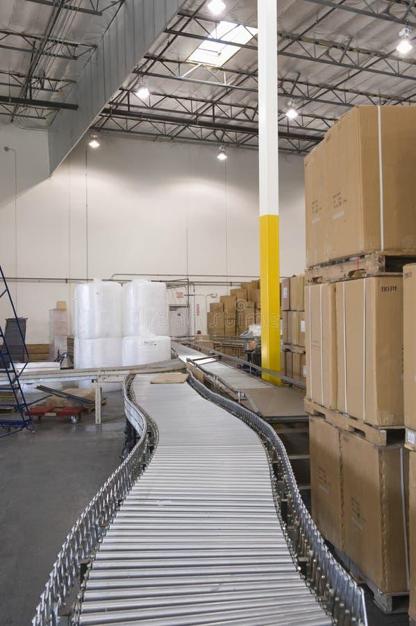 Boîtes et bande de conveyeur dans l'entrepôt images stock