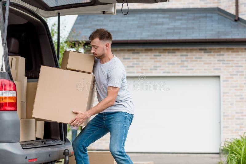 boîtes mobiles de jeune homme énergique de voiture dans nouveau image libre de droits