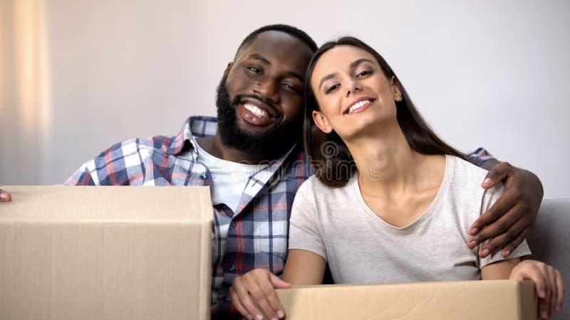 Boîtes multiraciales gaies de carton de participation de famille, prêtes à se déplacer en nouvel appartement photo libre de droits