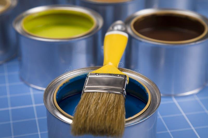 Boîtes ouvertes de peinture, brosse, fond bleu image libre de droits