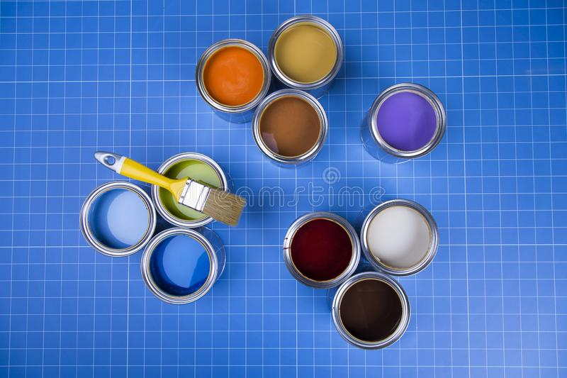 Boîtes ouvertes de peinture, brosse, fond bleu images stock
