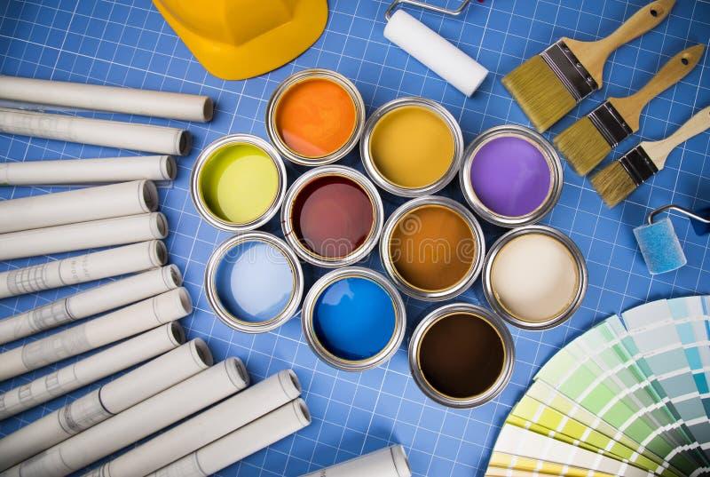Boîtes ouvertes de peinture, brosse, fond bleu photographie stock libre de droits
