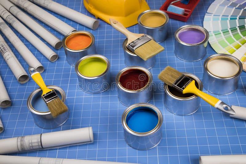 Boîtes ouvertes de peinture, brosse, fond bleu images libres de droits