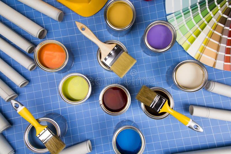Boîtes ouvertes de peinture, brosse, fond bleu photo stock