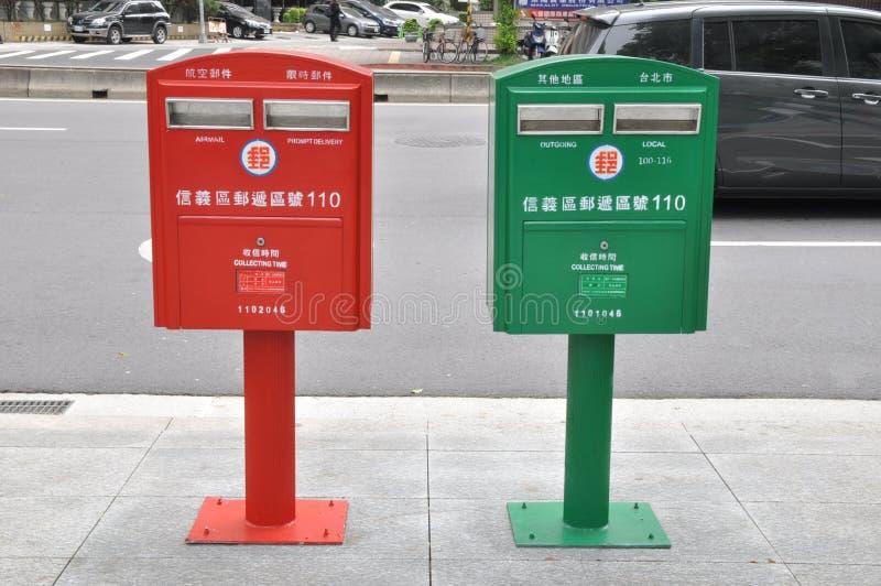 Boîtes rouges et vertes tranquilles de courrier photographie stock libre de droits