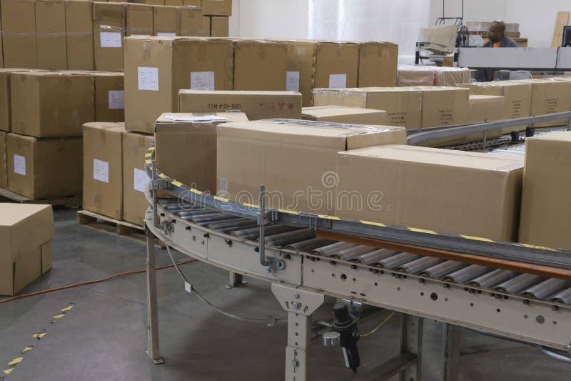 Boîtes sur la bande de conveyeur dans l'entrepôt photo stock