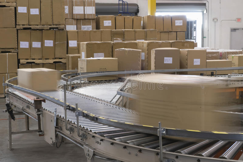 Boîtes sur la bande de conveyeur dans l'entrepôt photographie stock libre de droits