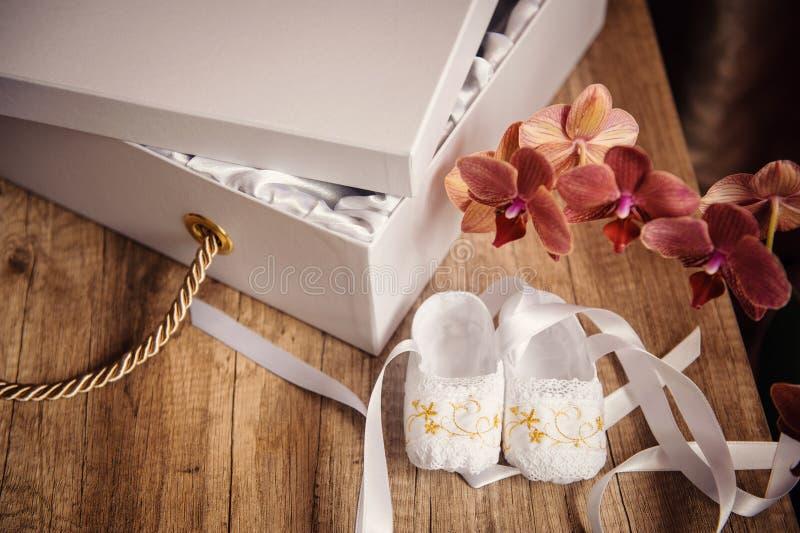 Boîtier blanc avec un cadeau et des chaussures d'enfants sur la table photo stock