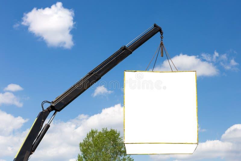 Boîtier blanc de maquette pour faire de la publicité accroché sur la grue contre le ciel bleu Placement de produit, copyspace pou photographie stock
